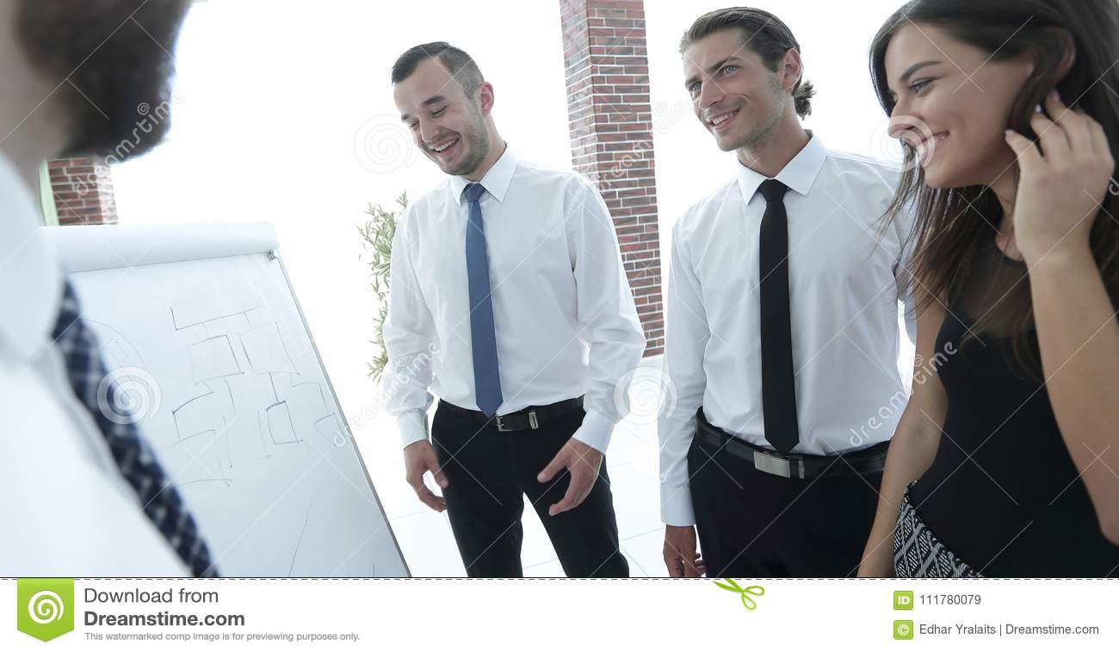 Businessman pointing business team on a blank flipchart.