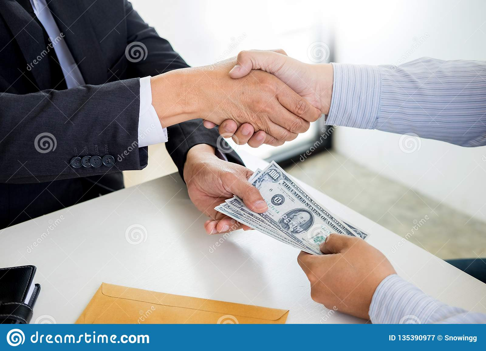 Businessman or politician taking bribe and Shaking Hands With Money in a suit, corruption trade exchange concept