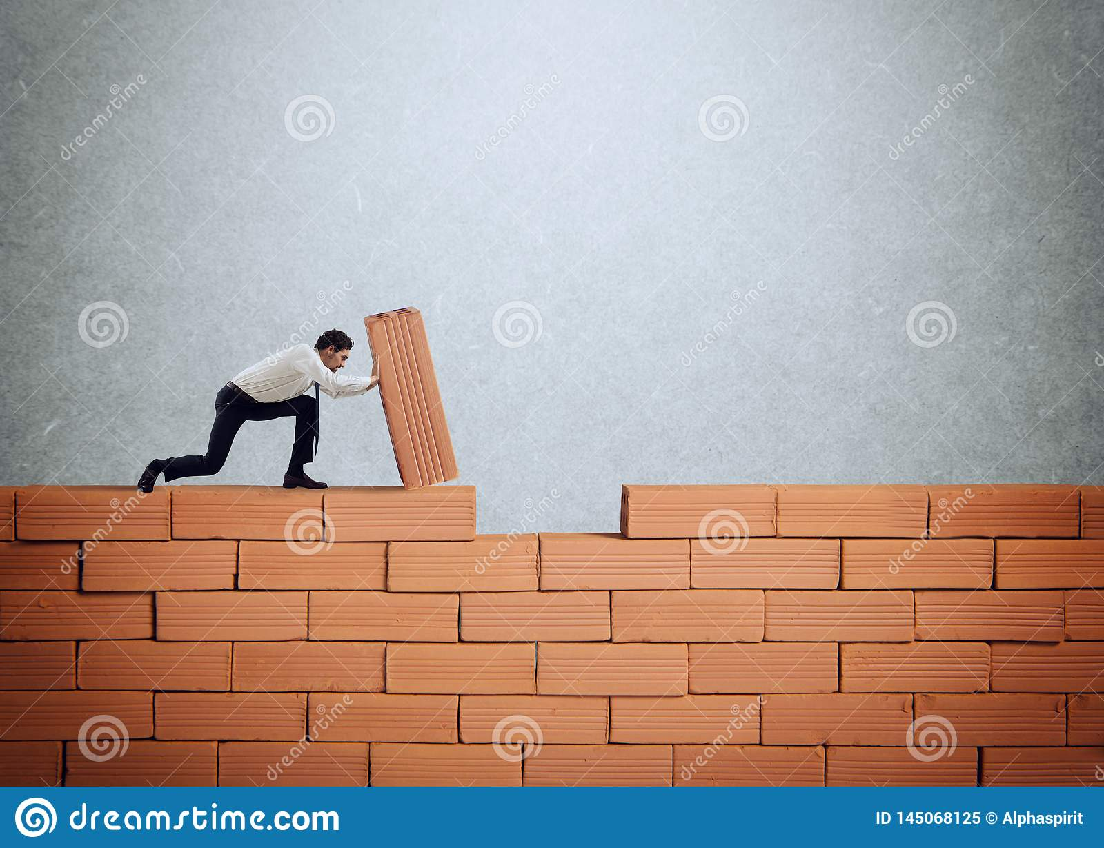 Businessman puts a brick to build a wall. Concept of new business, partnership, integration and startup