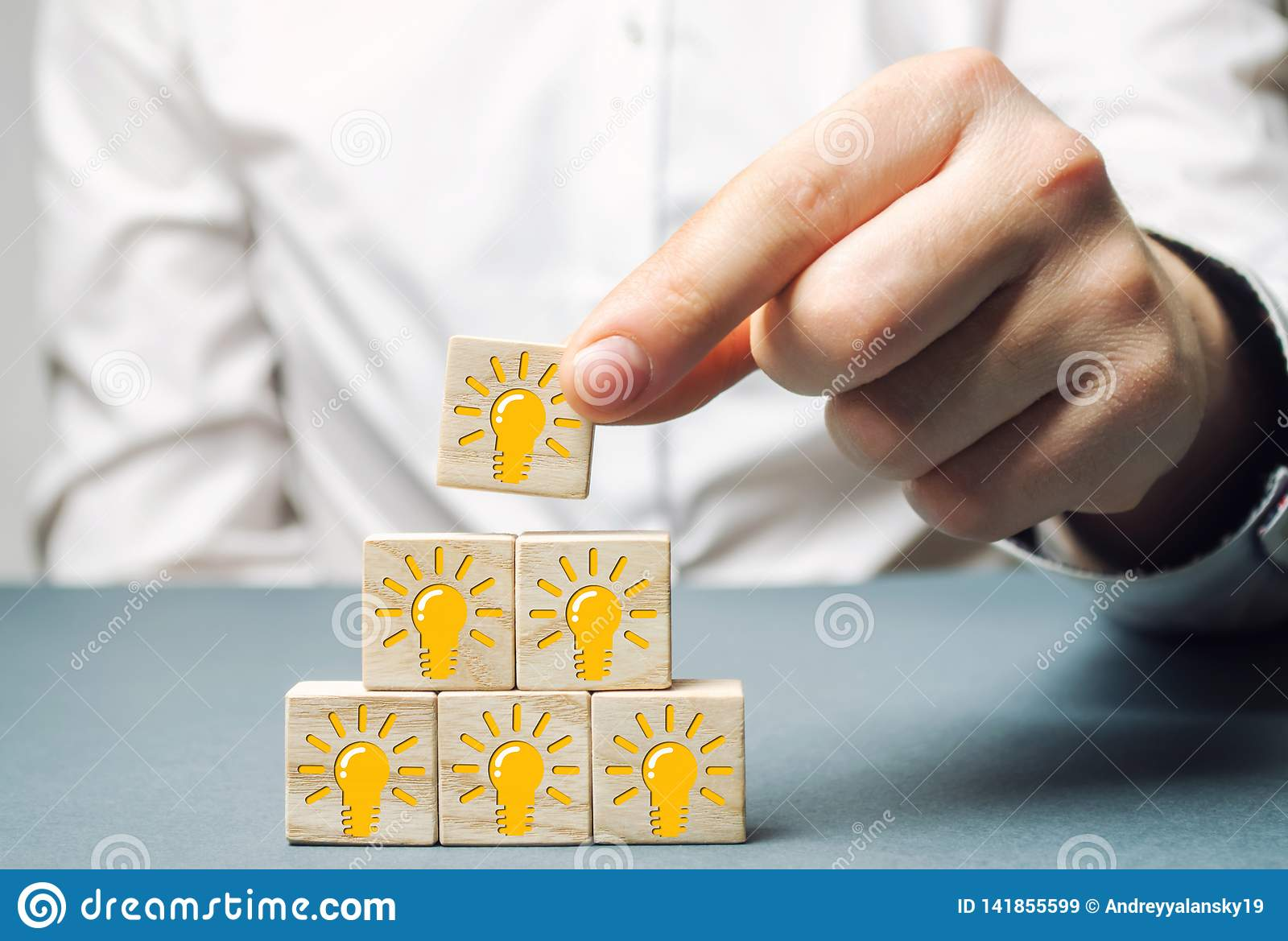 A businessman puts wooden blocks with a light bulb of an idea or inspiration. Generation of innovative business ideas. Creative
