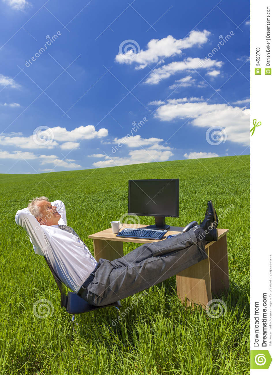 Businessman Relaxing Feet Up Desk In Green Field Stock ...