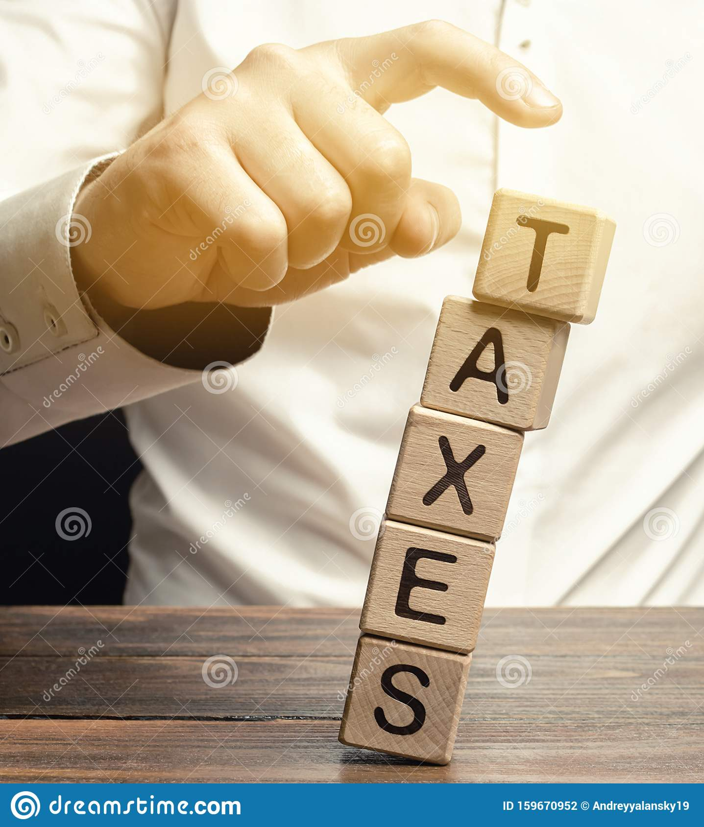 Businessman Removes Wooden Blocks With The Word Taxes. The Concept Of Tax Payment For