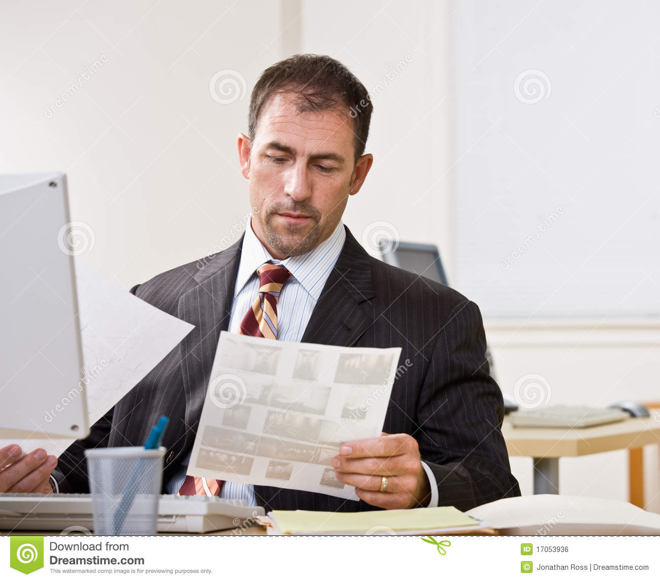 Businessman Reviewing Paperwork Royalty Free Stock Image - Image