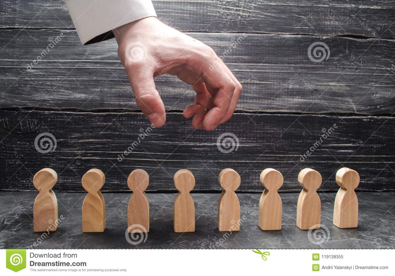The businessman`s hand hangs over the figures of people and prepares them to grab. The dismissal of workers, the destruction