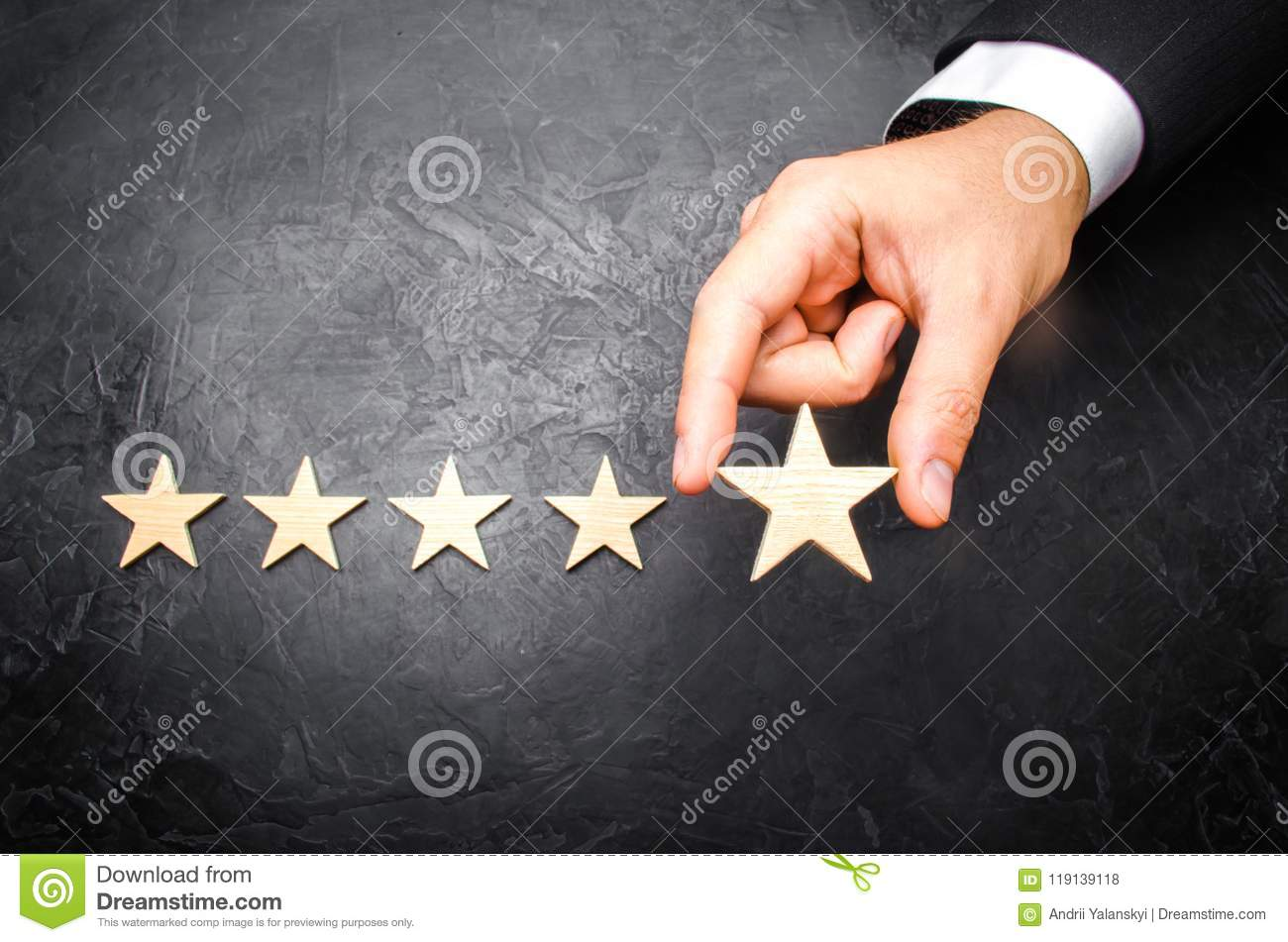 The businessman`s hand in the suit holds the fifth star. Get the fifth star. The concept of the rating of hotels and restaurants,