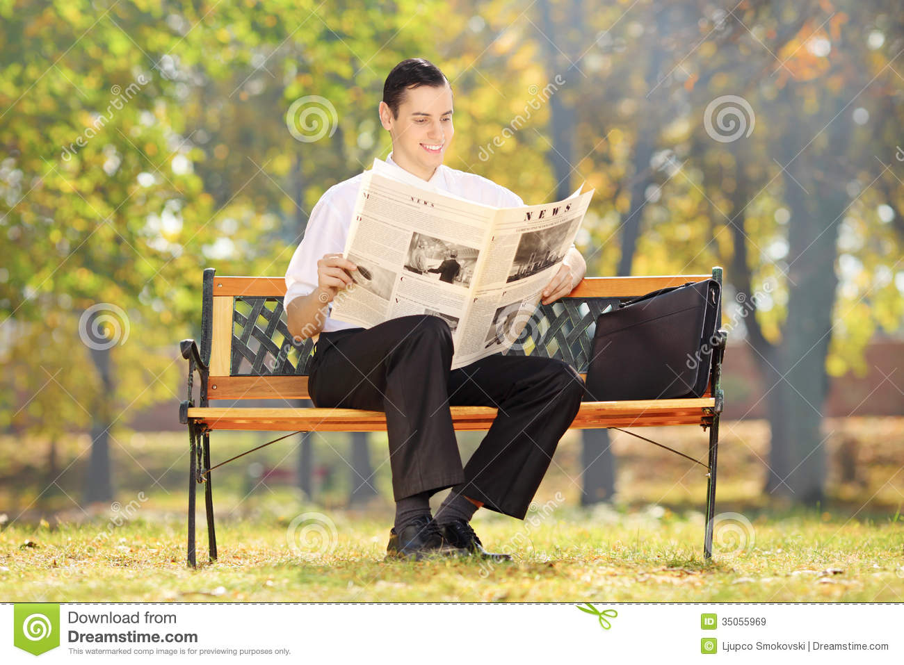 businessman seated on a bench reading a newspaper in a park stock