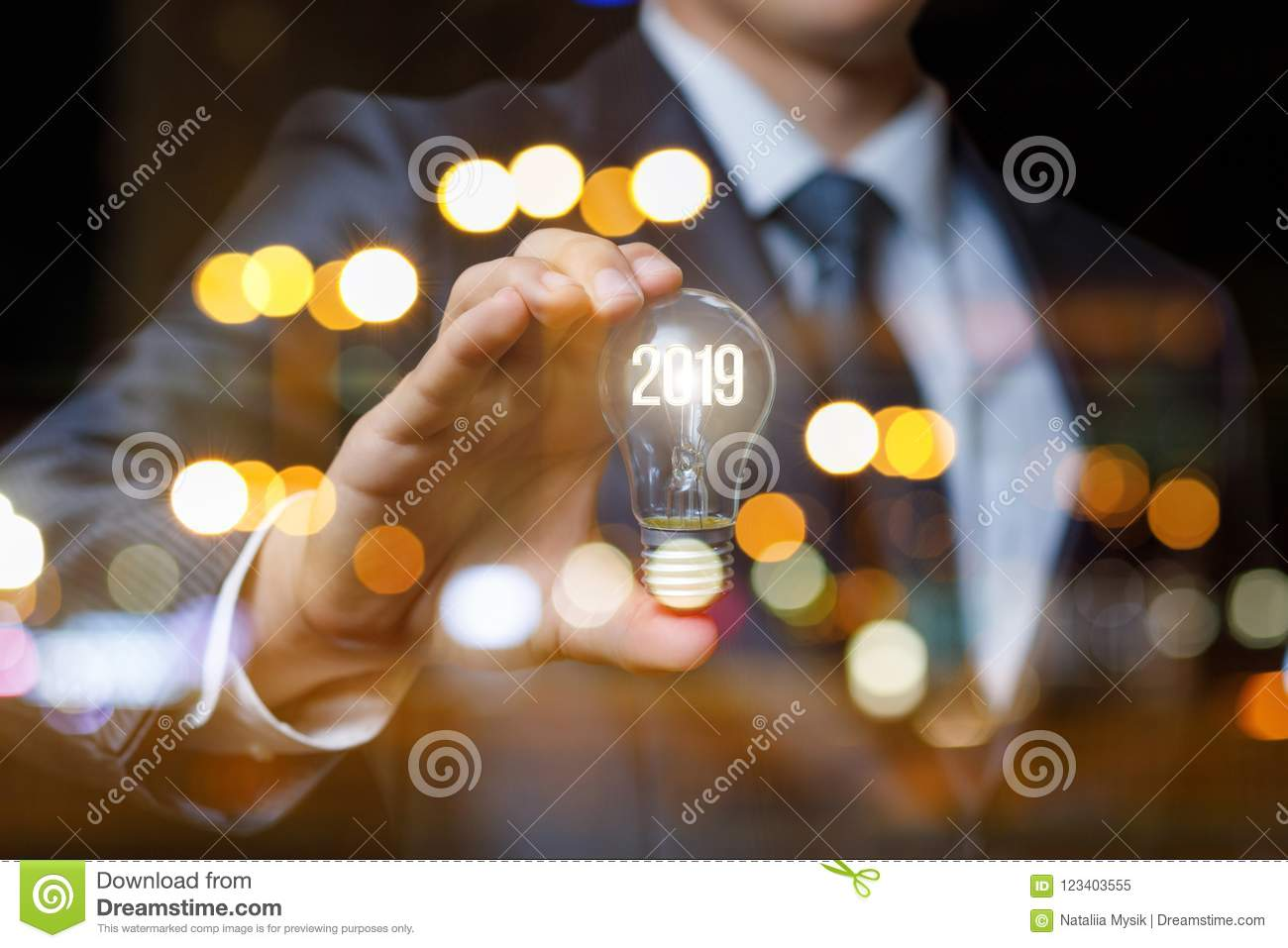 Businessman showing light bulb with glowing digits 2019.