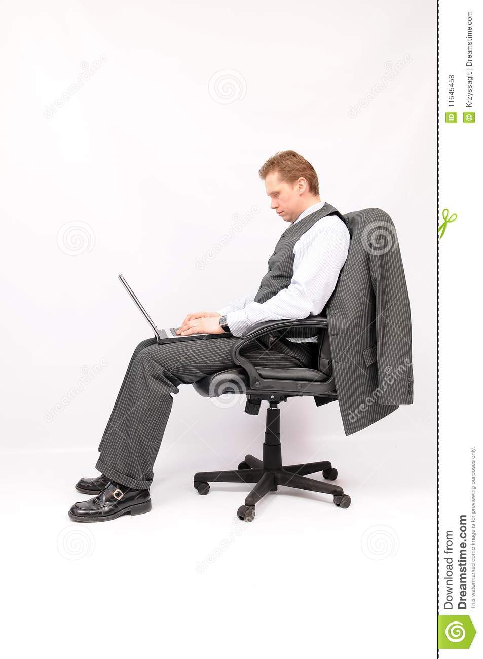 Businessman sitting in an armchair with a laptop royalty for Sitting in armchair