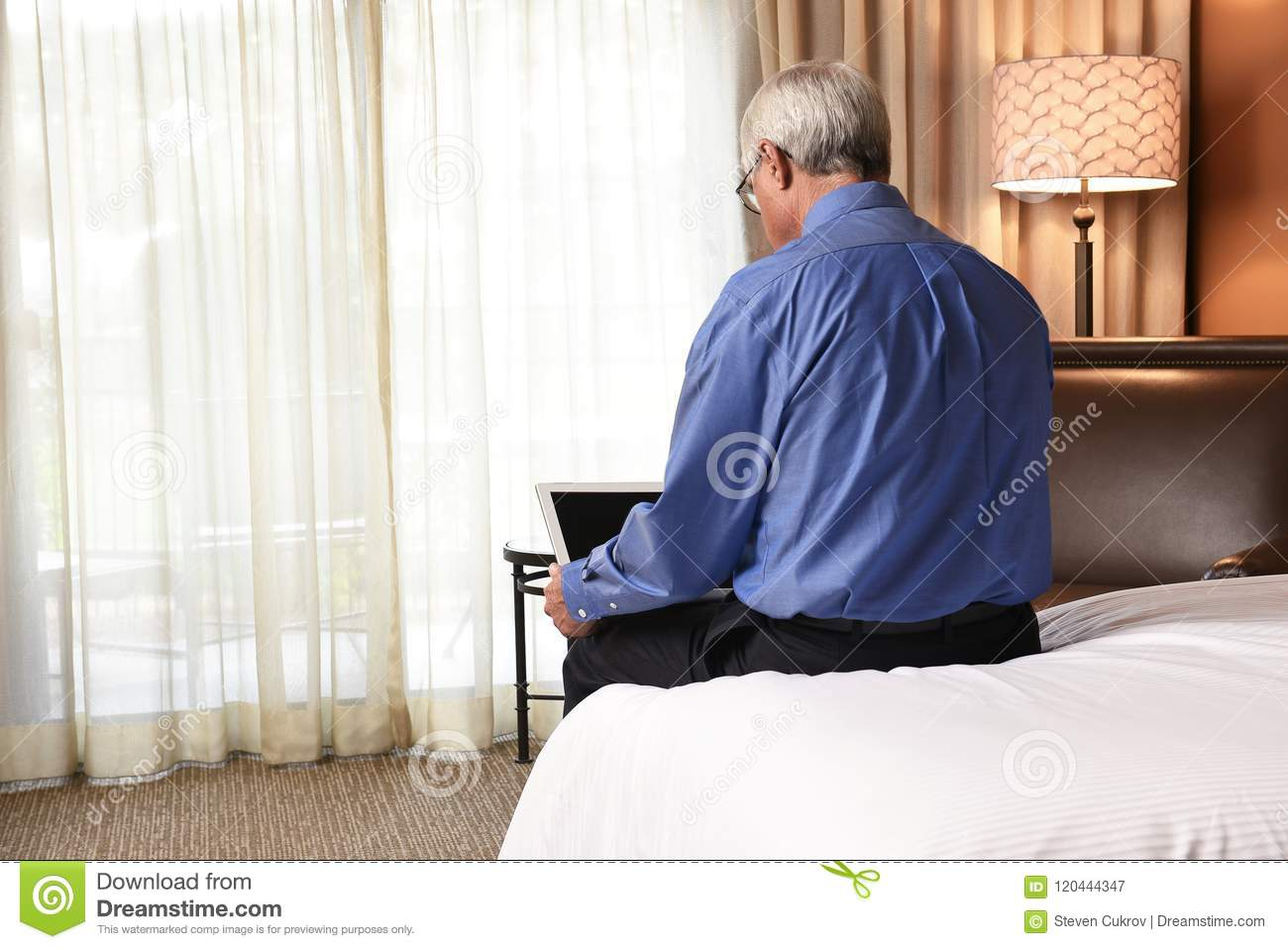 Businessman sitting on the bed in his hotel room using his laptop