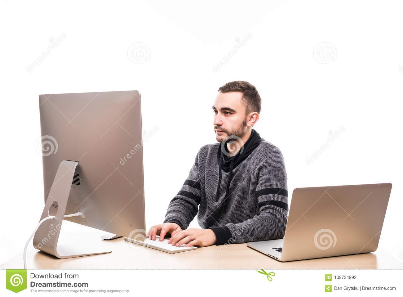 Businessman Sitting Behind Desk At Work Looking At Monitor