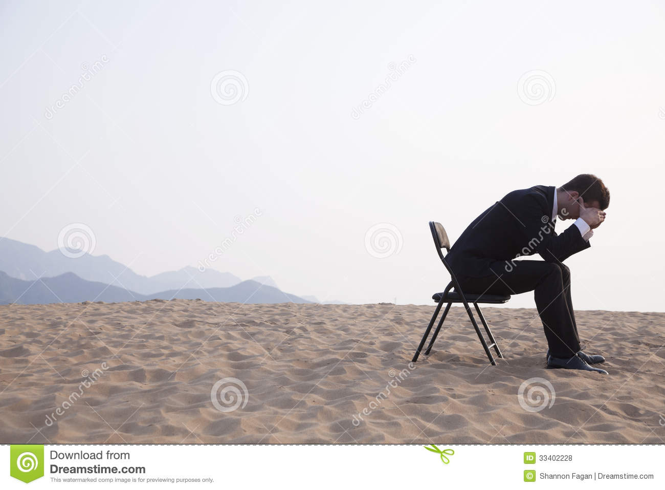 Businessman Sitting With His Head In His Hands In The