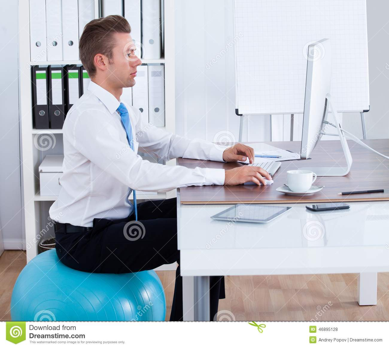 Businessman Sitting On Pilates Ball And Using Computer ...