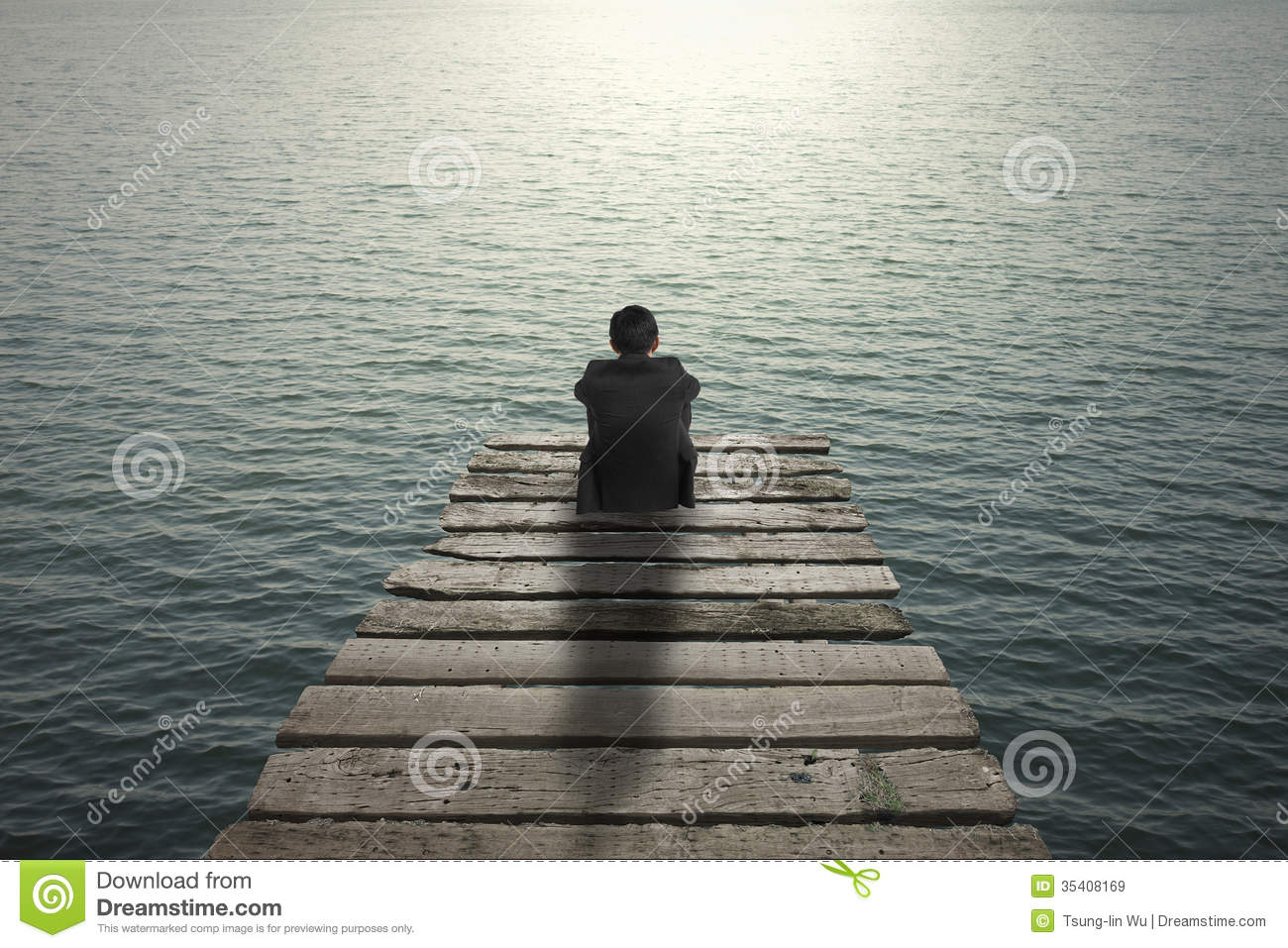 Businessman Sitting And Thinking On Old Wooden Pier To The