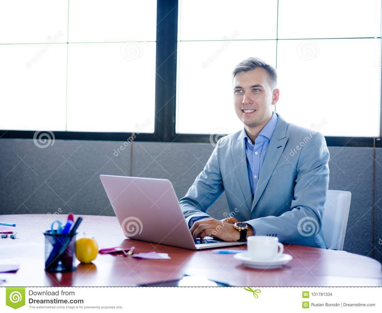 Businessman Sitting Working Behind Laptop At Office Desk In
