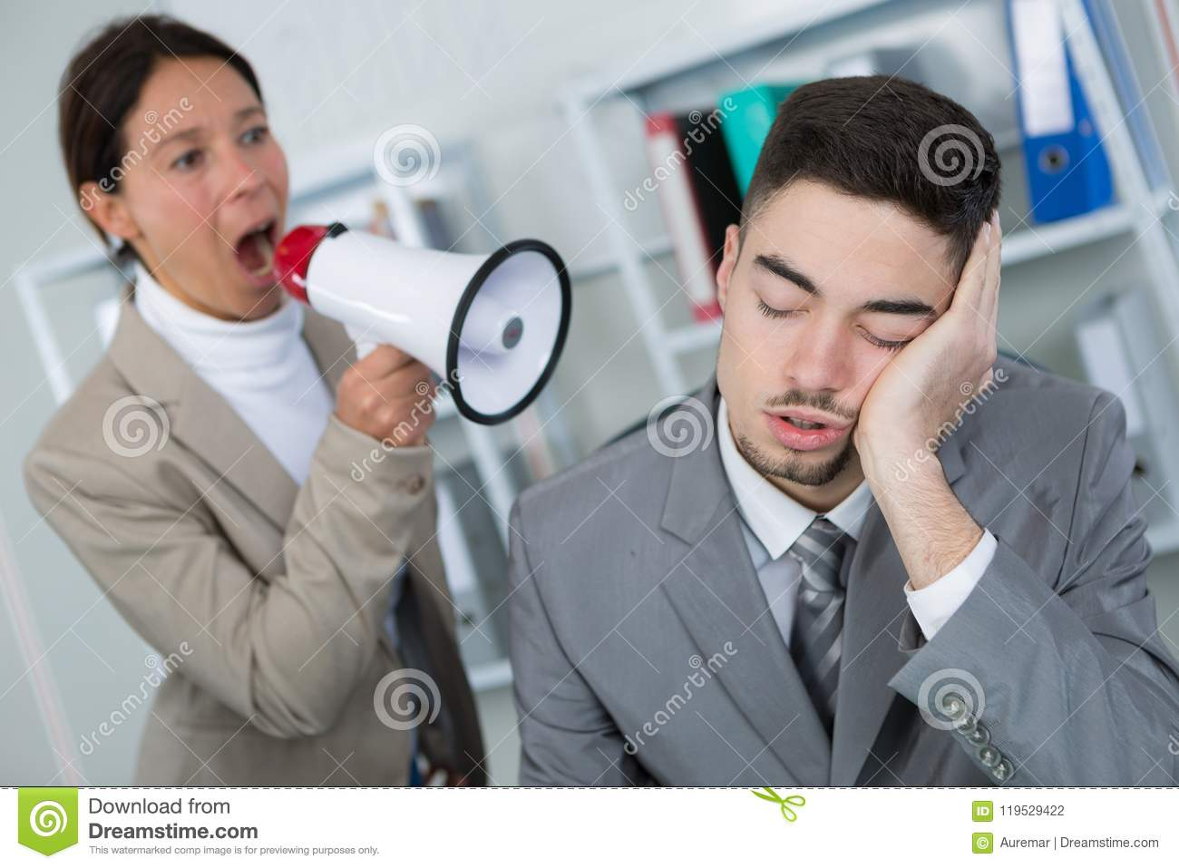 Businessman sleeping at workplace and businesswoman waking him up