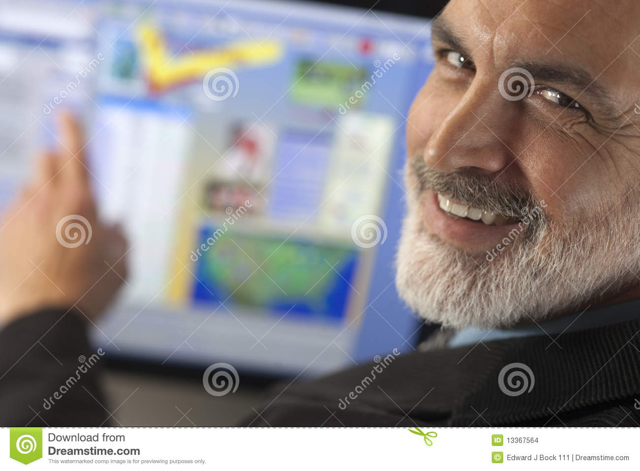 Businessman Smiling and Pointing to Computer Monit