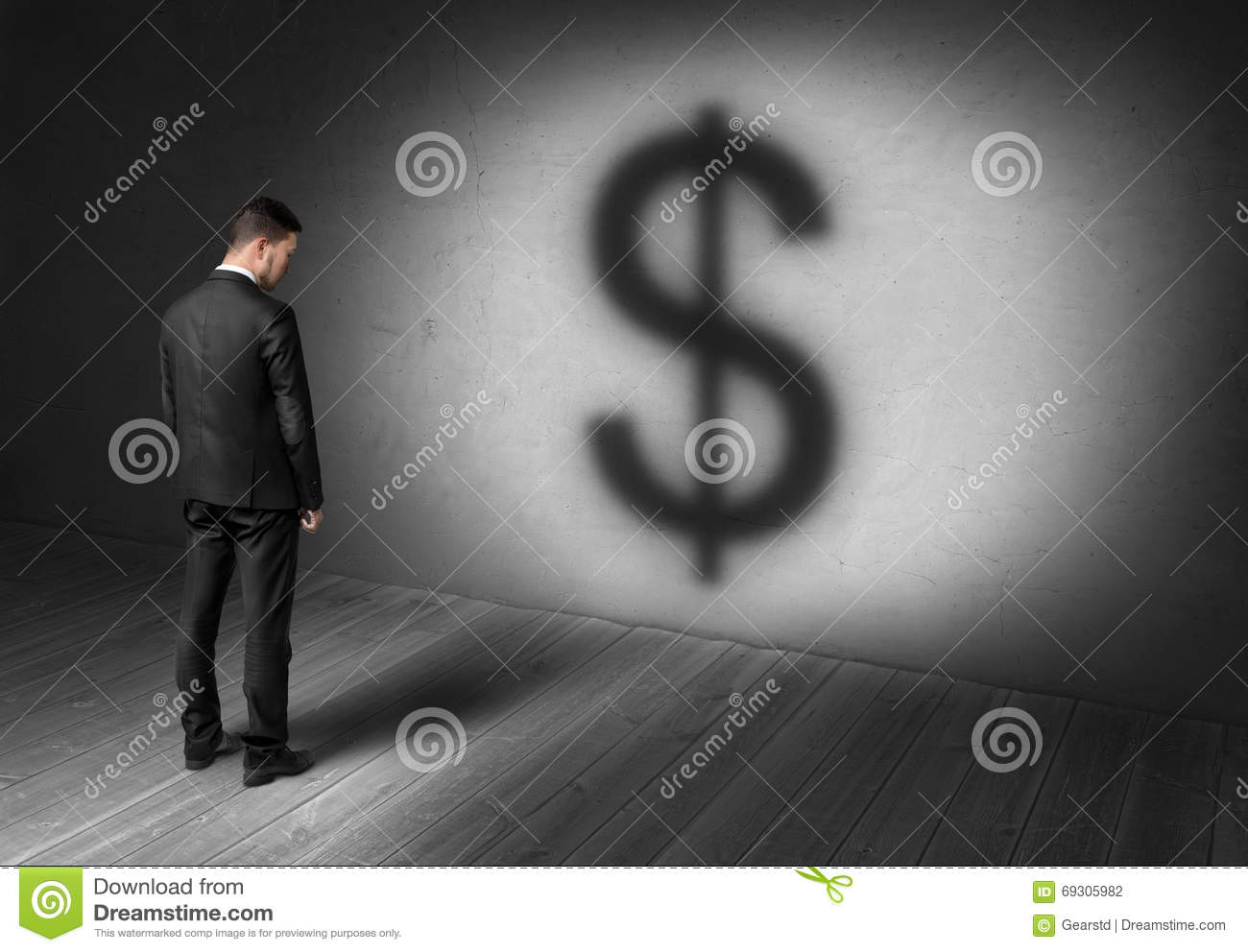 Businessman standing in front of concrete wall on spotlight with big dollar sign looking like shadow