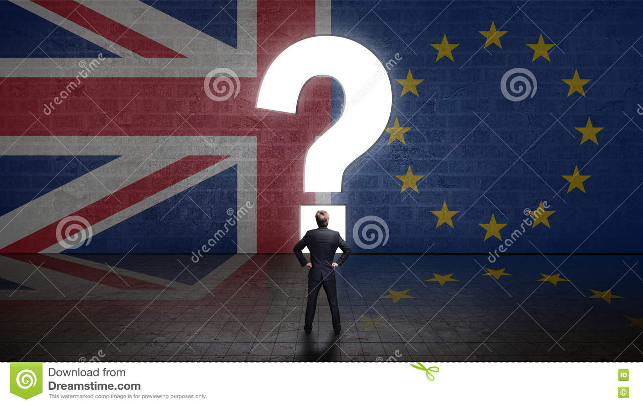 Businessman standing in front of a wall with the union jack and the eu flag with question-mark portal