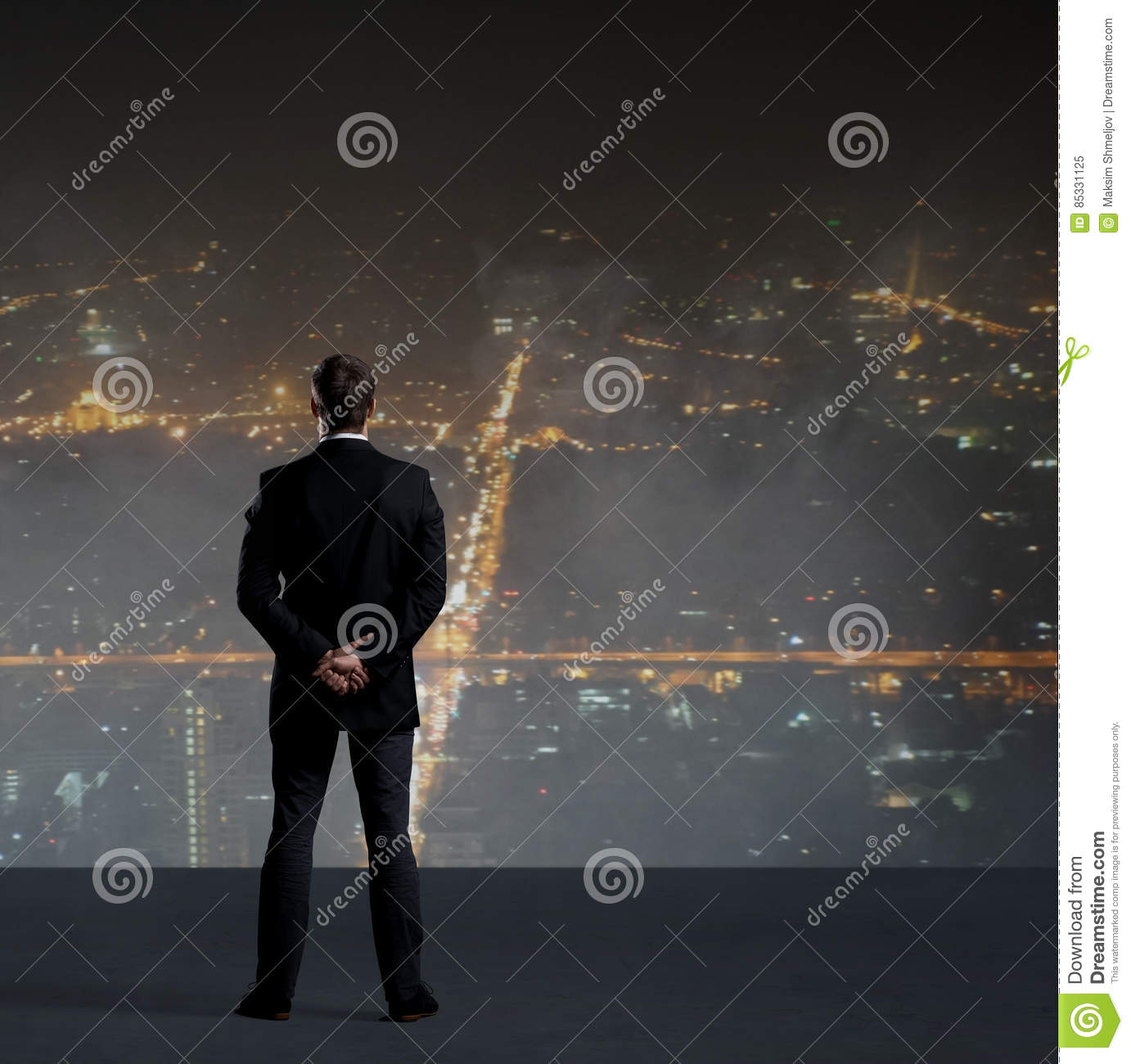 Businessman standing over night city background.