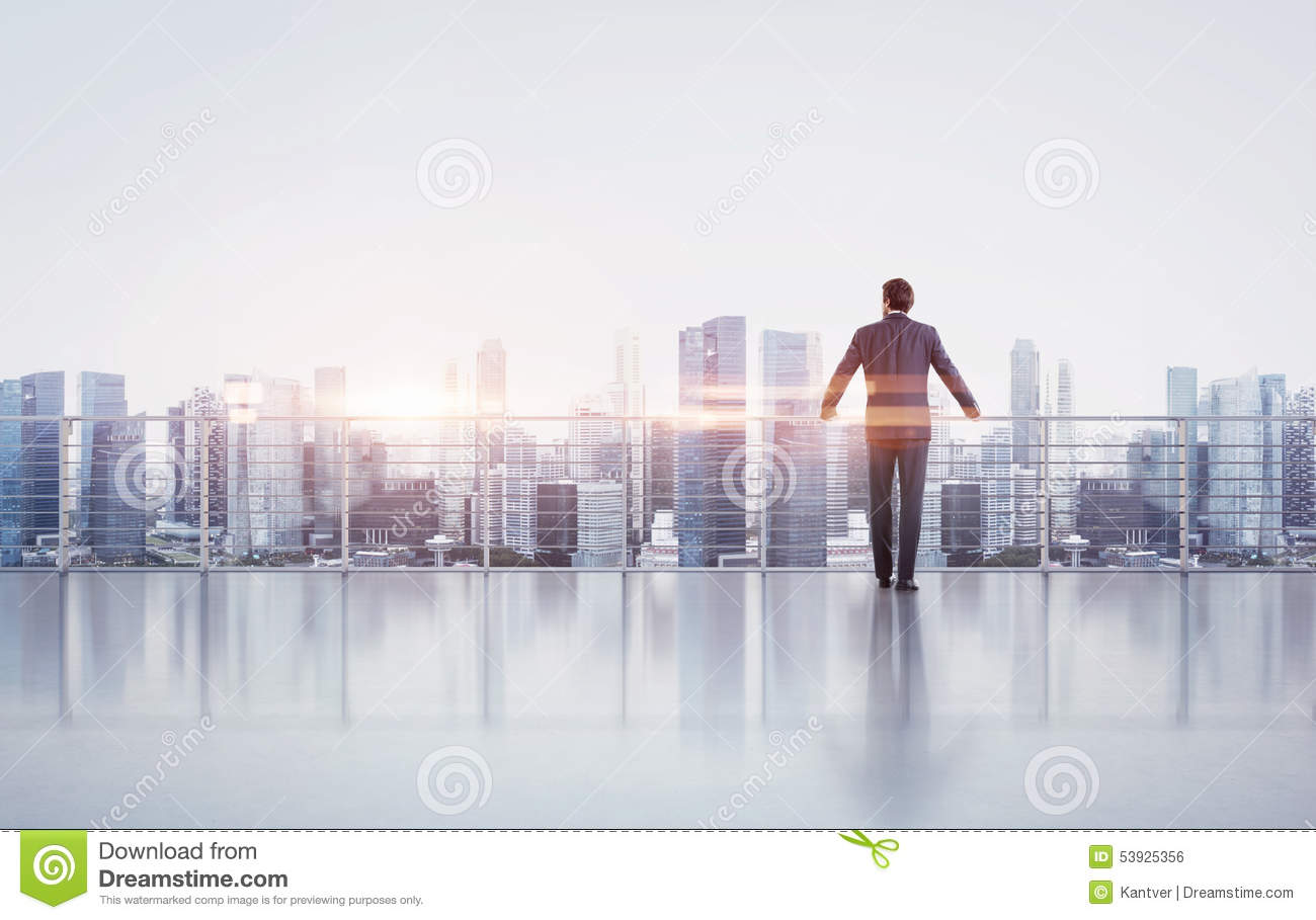 Businessman standing on a roof and looking at