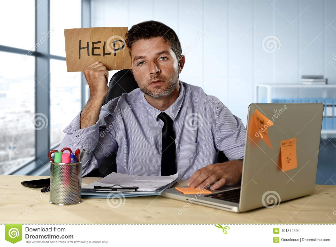 Businessman suffering stress working at computer desk holding sign asking for help looking tired exhausted