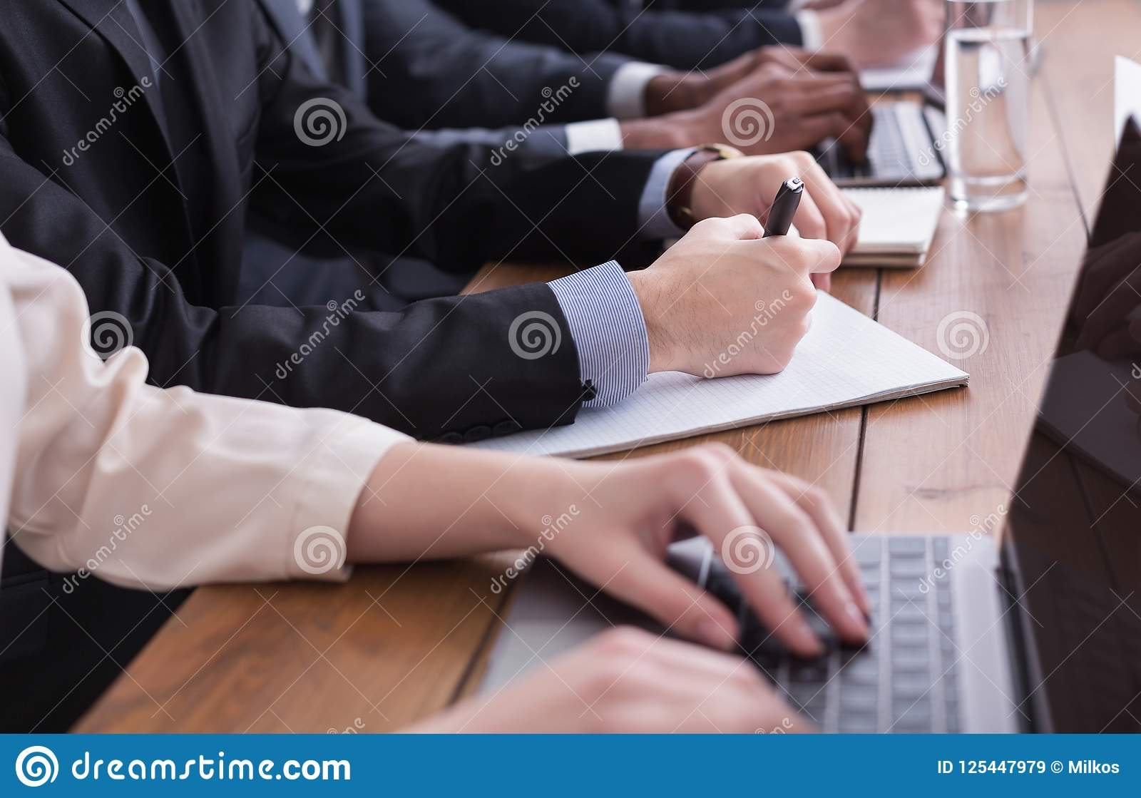 Businessman in suit putting signature on contract