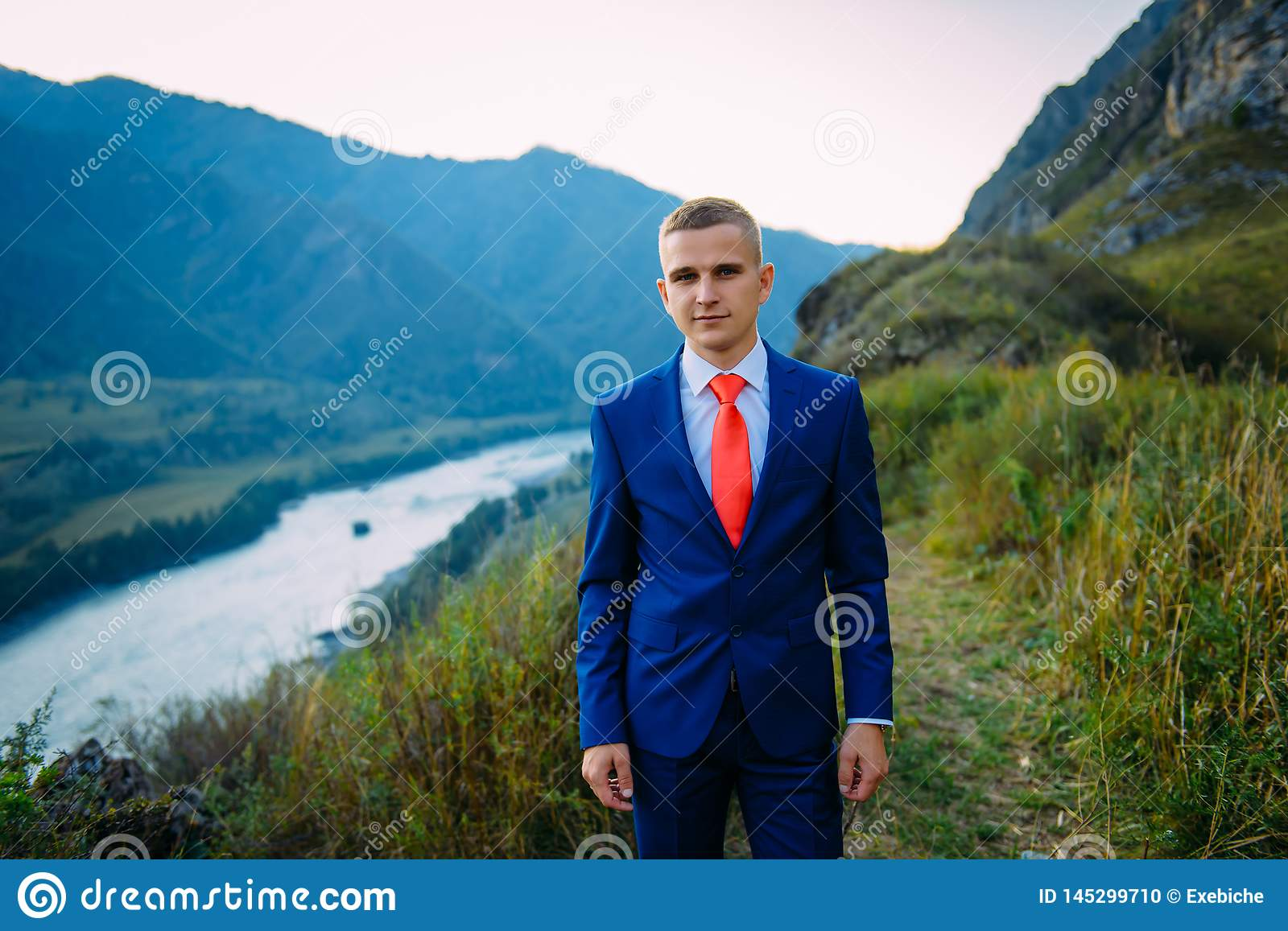 Businessman in a suit with red tie on the top of the world with background of mountains