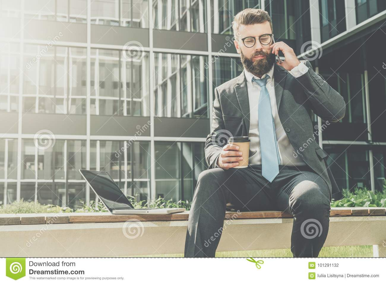 Businessman in suit and tie is sitting outside on bench,drinking coffee and talking on his cell phone.Nearby is laptop.