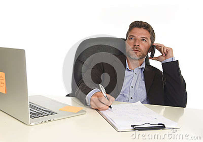 Businessman in suit working at laptop computer desk talking on mobile phone at modern office