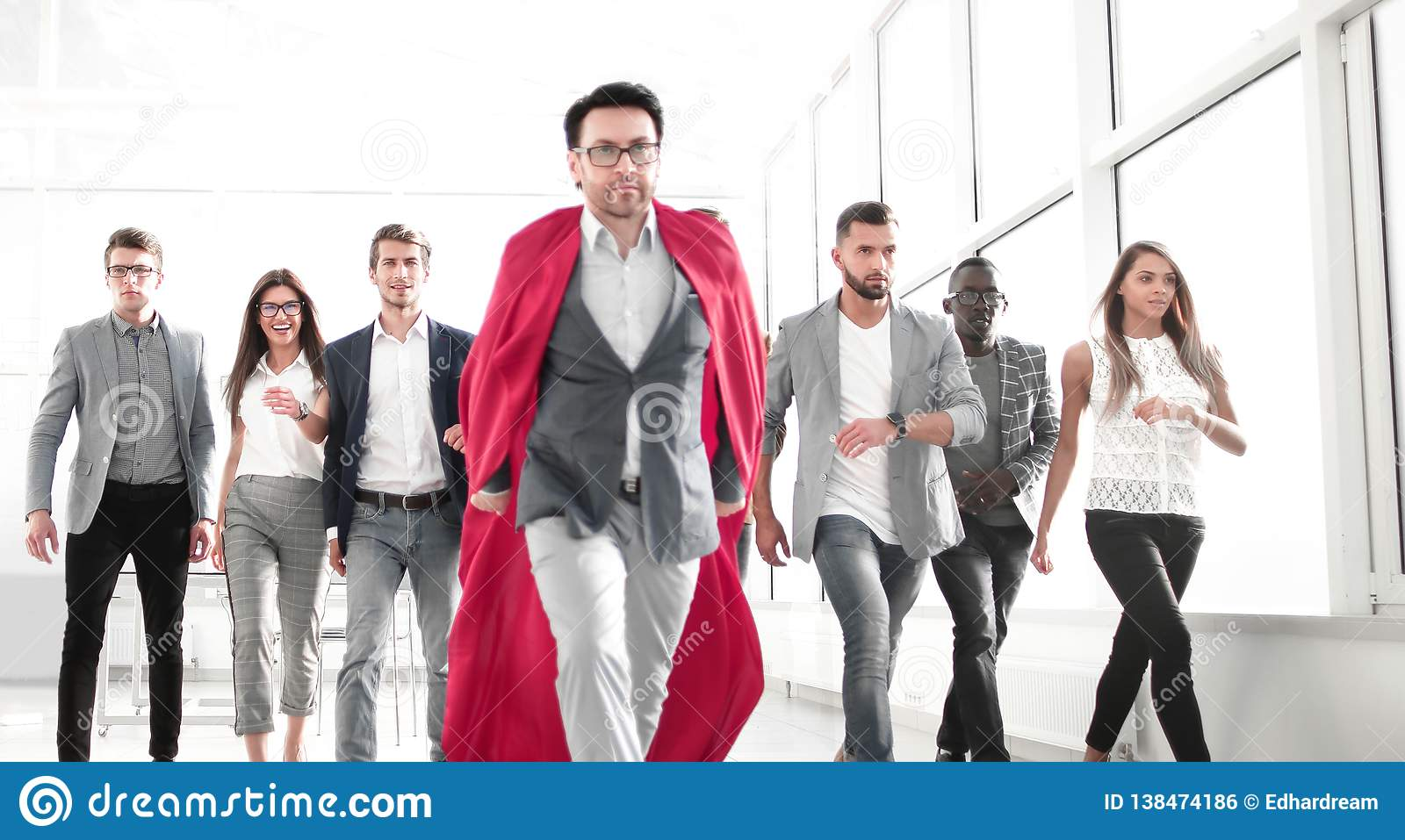 Businessman in a superhero`s cloak is ahead of the business team