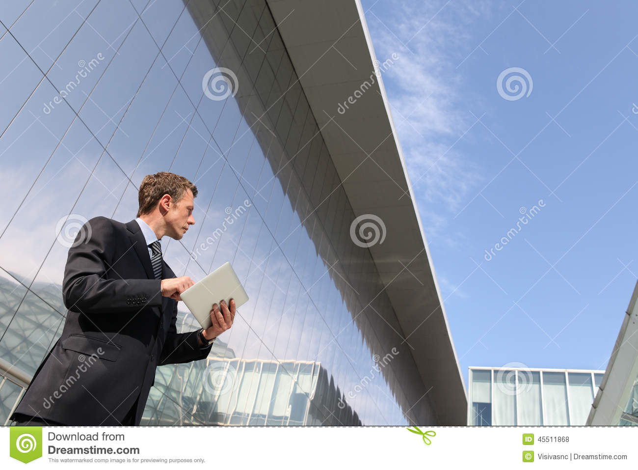 Businessman with tablet that looks far into the sky, in a scene of urban building, cloud computing