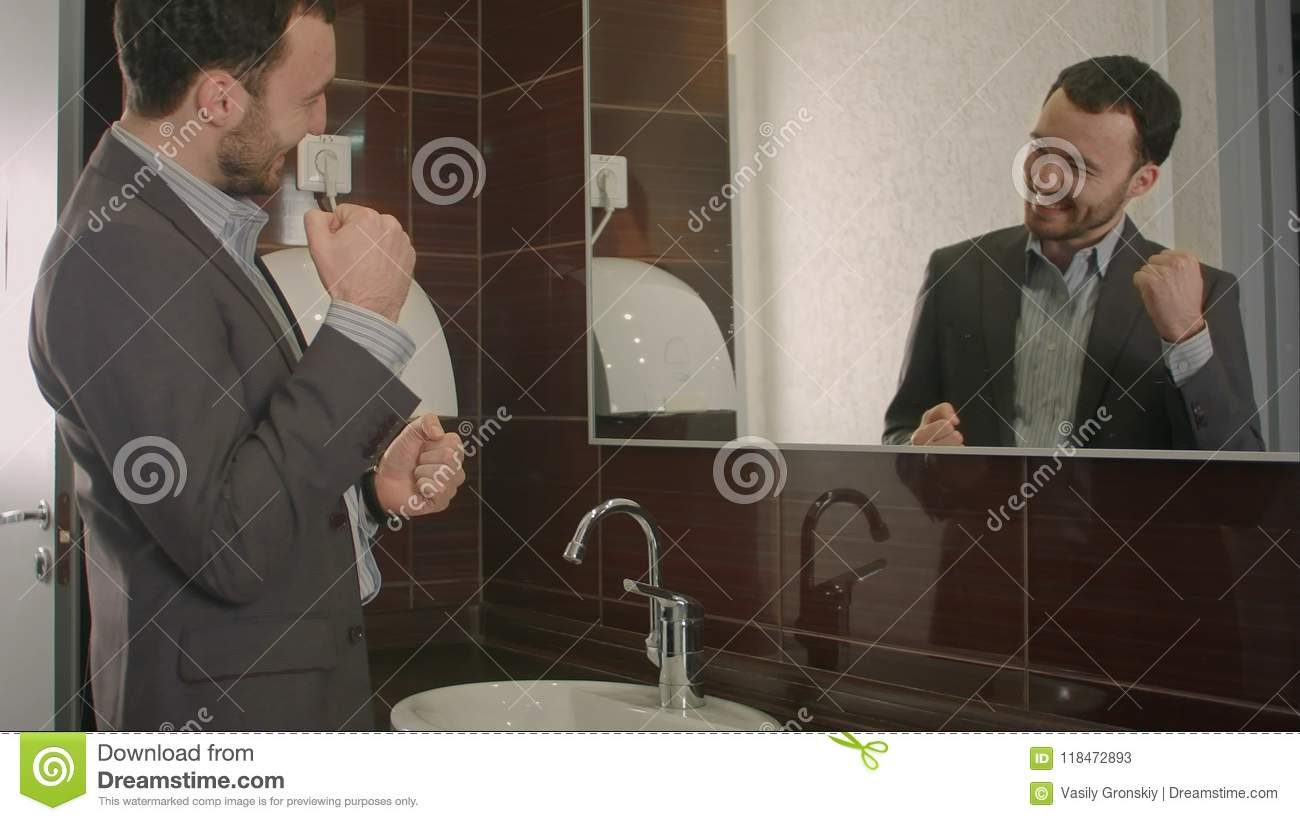 Businessman takes a look at himself in the mirror.