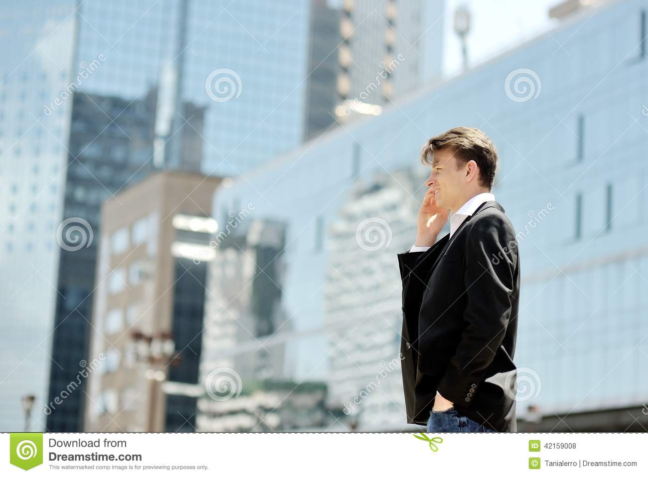 Businessman talking on cell phone on background modern office corporate buildings