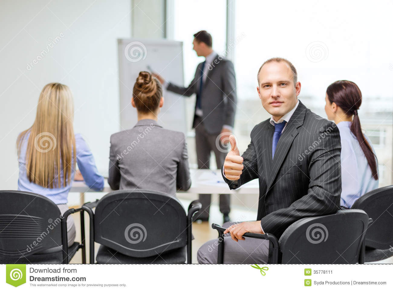 Businessman with team showing thumbs up in office stock for Office photos