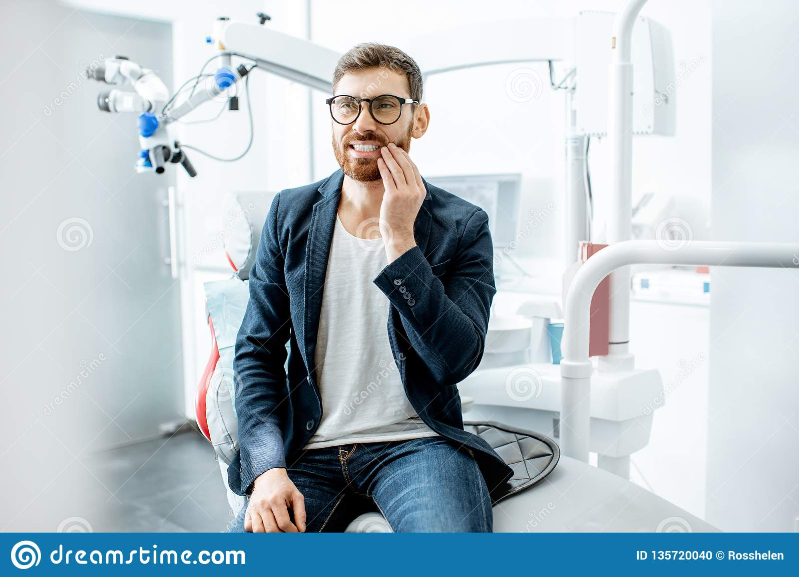 Businessman with toothache in the dental office
