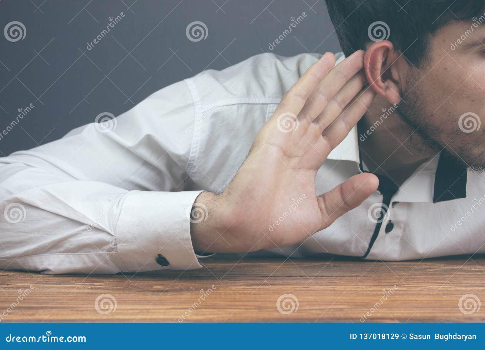 Businessman trying to hear gossip