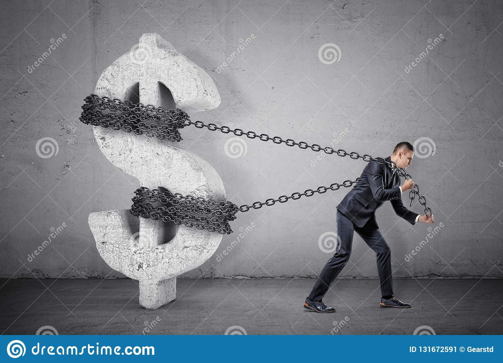 A businessman tugs at a chain trying to move a large concrete dollar sign from its place.