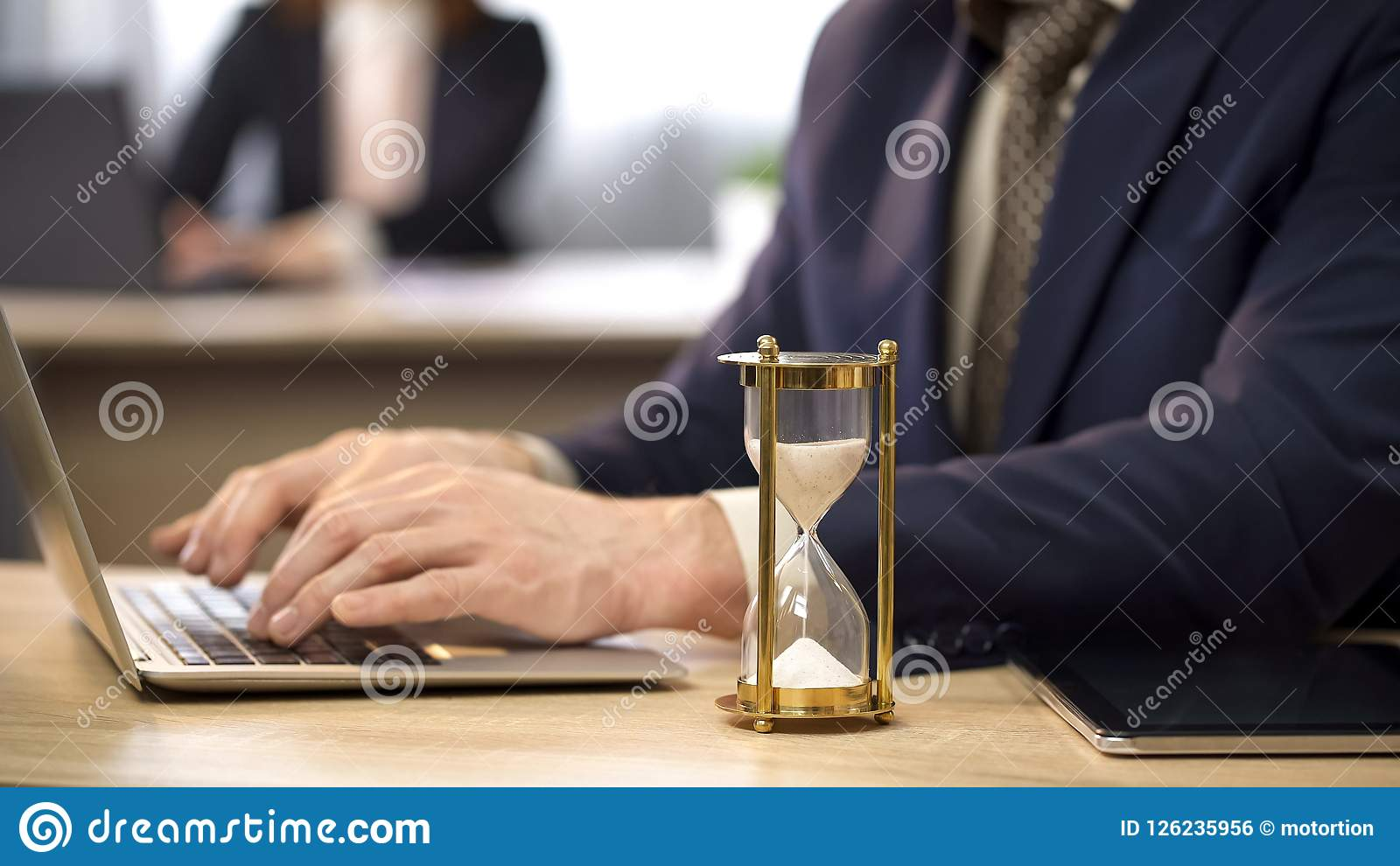 Businessman typing on laptop at desk, hourglass trickling, deadline approaching