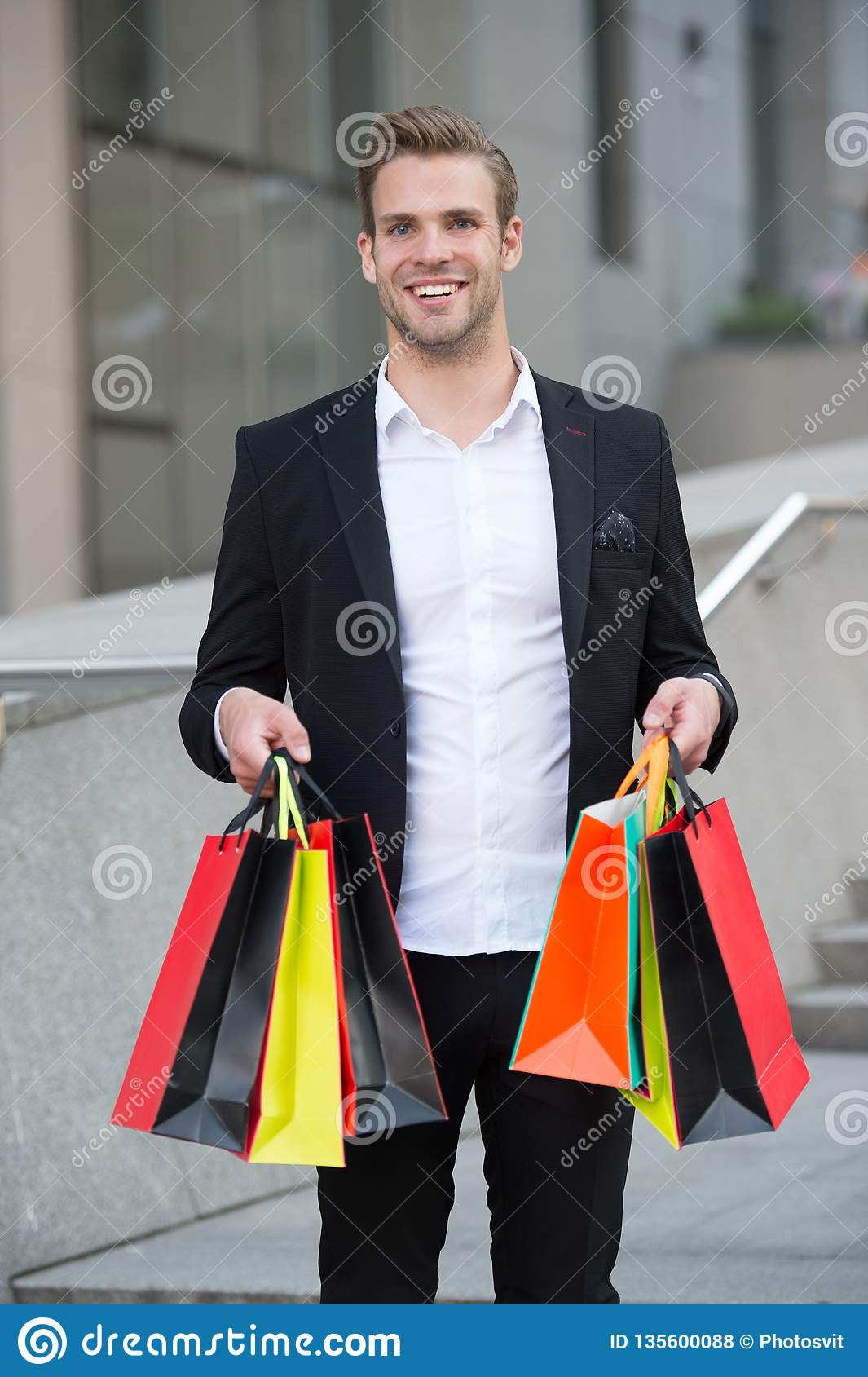 Businessman use shopping application. Man carries shopping bags urban background. Successful businessman shopping online