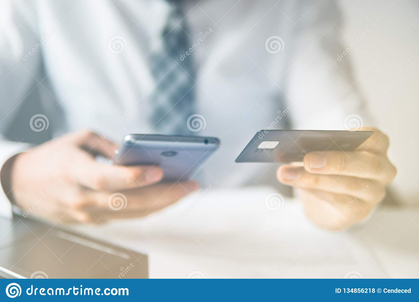64f2b13df99 Businessman uses credit card and a smartphone. Shopping online. Mobile phone.  Online payment.