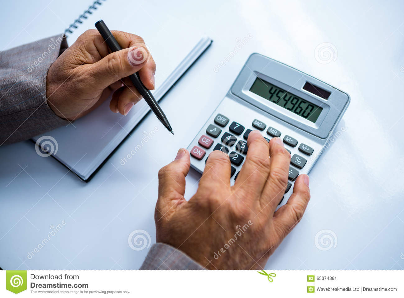 Businessman Using Calculator And Taking Notes Stock Photo