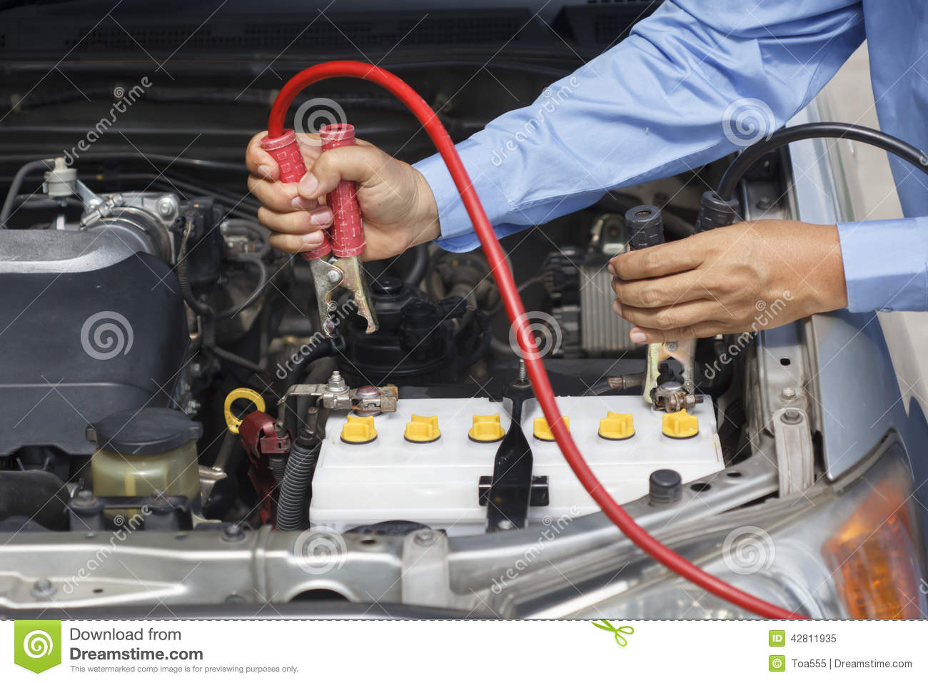 Businessman using jumper cables to start a car