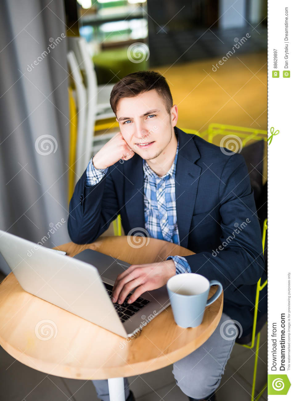 Businessman using laptop with tablet and pen on wooden table in coffee shop with a cup of coffee view from above