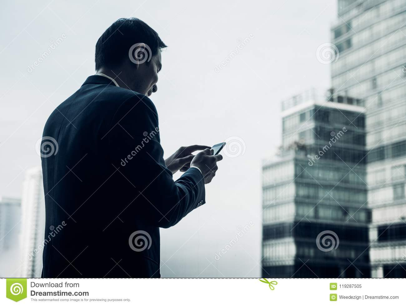 businessman using mobile phone near office window at office building,online business concept.