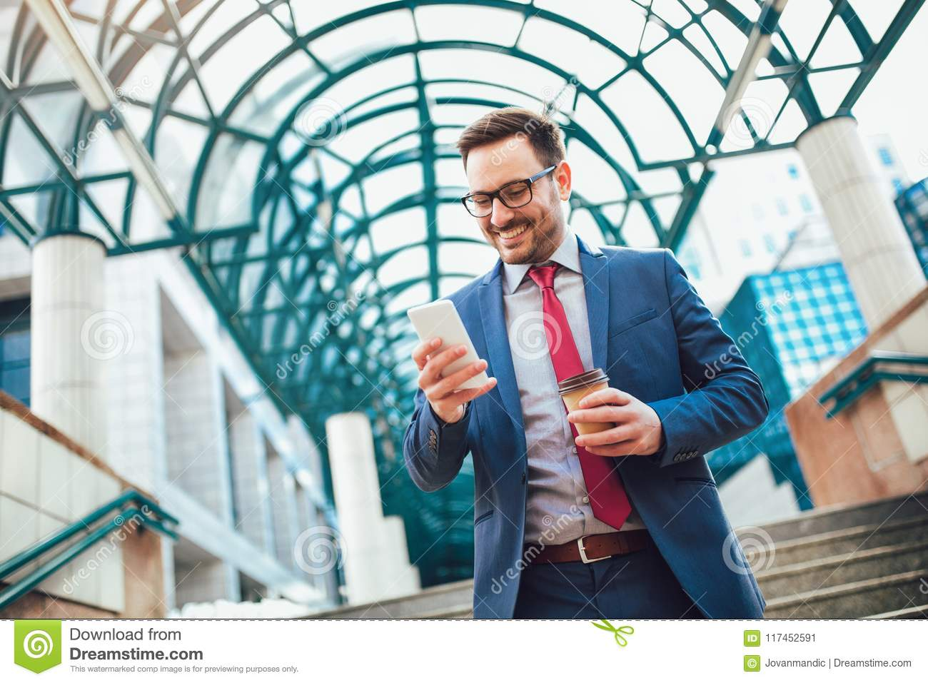 be0371bbb5 Businessman using mobile phone outside of office buildings in the  background. Young caucasian man holding smartphone for business work and  drink coffee to ...