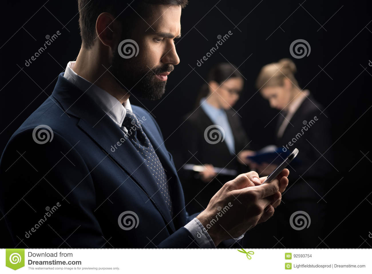 Businessman using smartphone while business people connecting behind