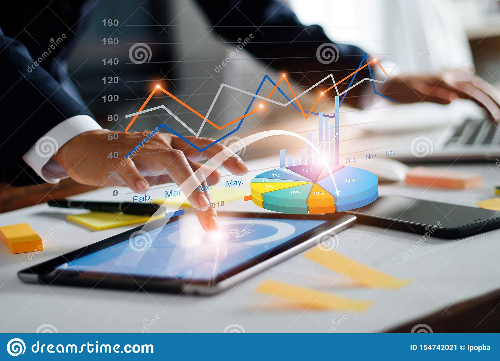 Businessman using tablet and laptop analyzing sales data and economic growth graph chart. Business strategy. Digital marketing.