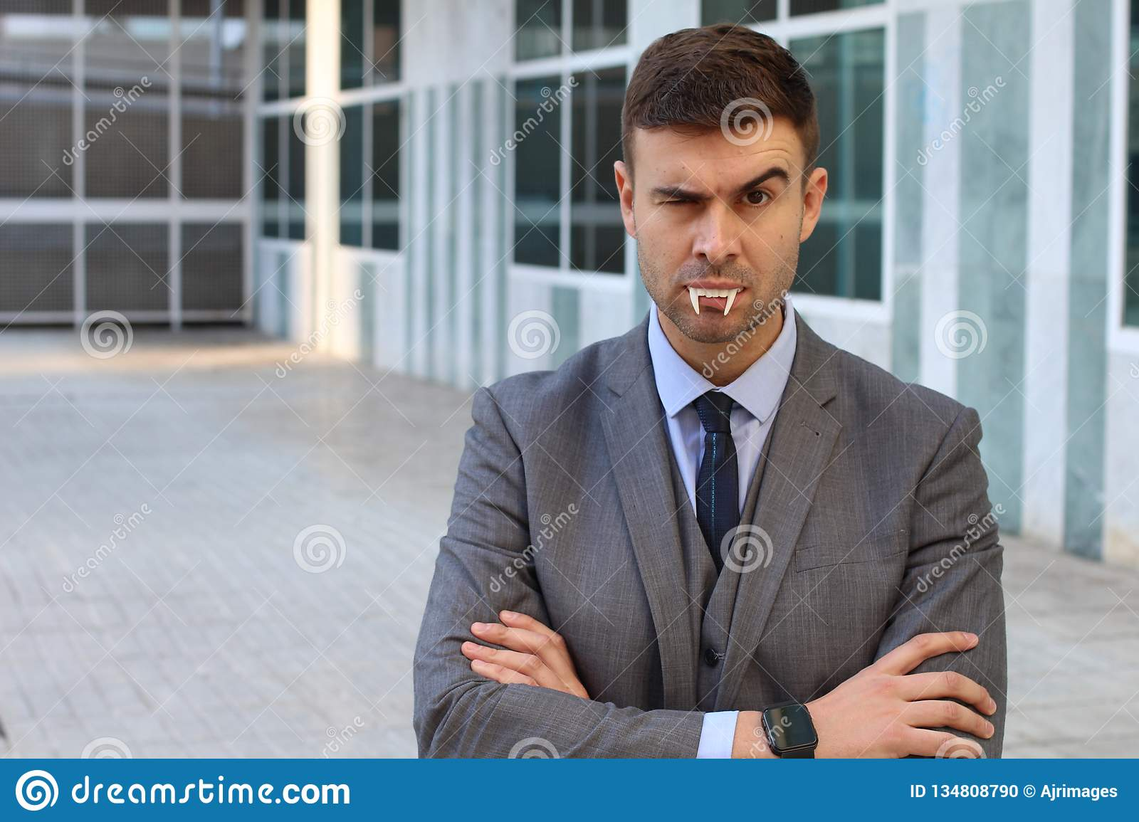 Businessman with vampire fangs in the office