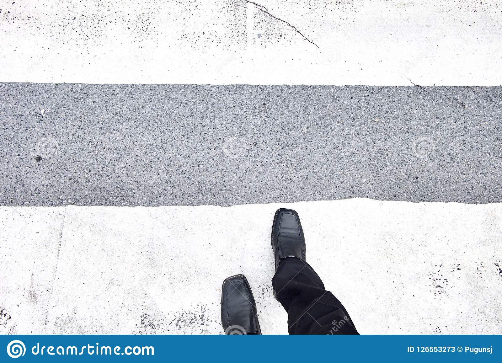 Businessman walking across the crosswalk. Black leather shoes and black slacks. Top view.