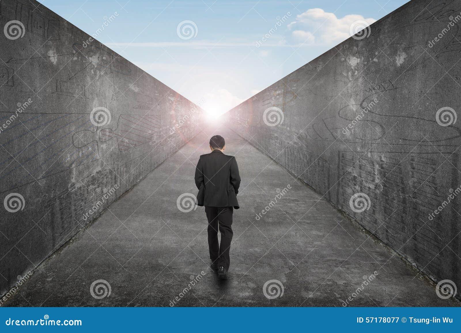 Businessman walking one way road toward exit sun sky view